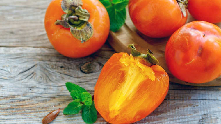 Delicious persimmon fruit and mint on a wooden background.